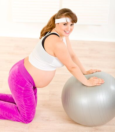 Happy beautiful pregnant woman doing exercises on  fitness ball at living room  photo