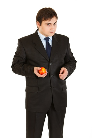 sagacious: Thoughtful modern businessman holding apple in hand isolated on white  Stock Photo