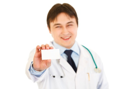 Smiling medical doctor holding blank business card in hand isolated on white  photo
