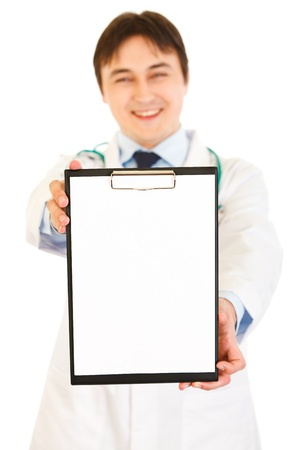 Smiling medical doctor holding blank clipboard isolated on white  photo