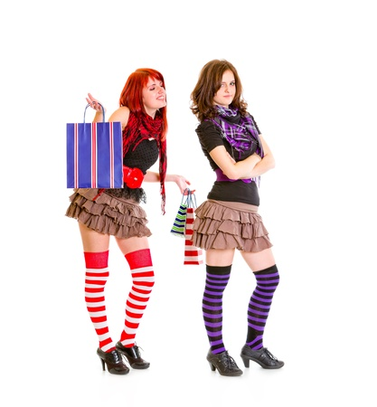 malcontent: Happy young girl with shopping bags standing behind her dissatisfied girlfriend isolated on white