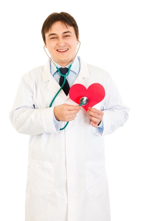 Smiling medical doctor holding stethoscope on paper heart isolated on white