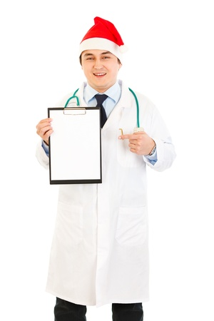 heal new year: Smiling medical doctor in Santa hat pointing finger at blank clipboard isolated on white