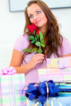 Dreamy pretty woman sitting among gifts and holding rose in hands Stock Photo - 9185156
