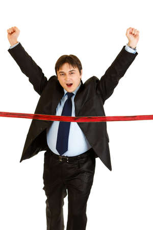 Pleased young businessman  crossing finish line isolated on white. Concept - success achievement  photo
