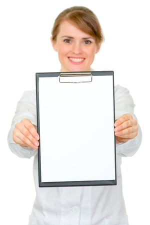 Smiling medical female doctor holding blank clipboard in hands isolated on white  photo