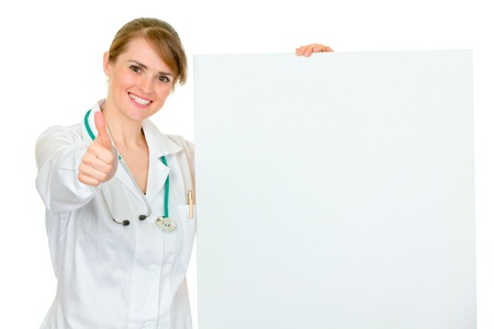 Smiling medical female doctor holding blank billboard and showing thumbs up gesture isolated on white Stock Photo - 9246904