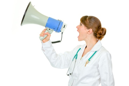 uptight: Frustrated medical doctor woman yelling through megaphone isolated on white  Stock Photo