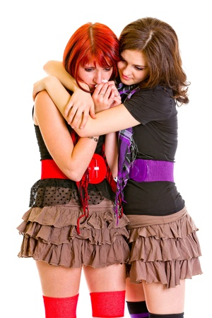 solicitous: Attentive young girl hugging and calming her sad girlfriend isolated on white  Stock Photo
