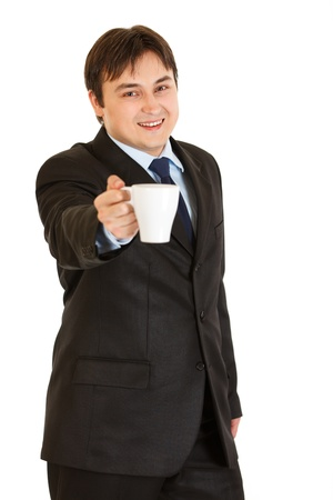 Smiling modern businessman offering cup of coffee  isolated on white  photo