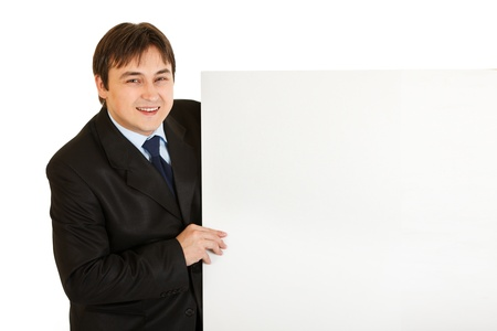 Pleased modern businessman holding blank billboard isolated on white  photo