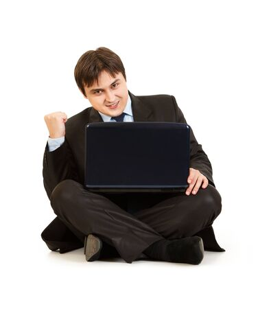 Excited modern businessman sitting on floor with laptop and rejoicing his success isolated on white  photo