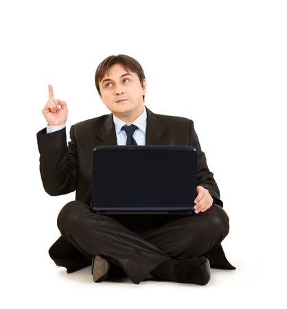 Thoughtful businessman sitting on floor with laptop and pointing finger up isolated on white. Idea gesture  photo