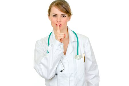 authoritative woman: Authoritative medical doctor woman with finger at mouth isolated on white. Shh gesture