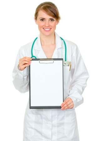 Smiling medical doctor woman holding blank clipboard in hands isolated on white  photo