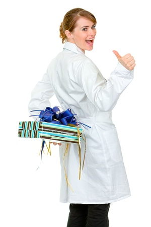 doctor holding gift: Happy medical doctor woman holding gift behind her back and thumbs up  isolated on white