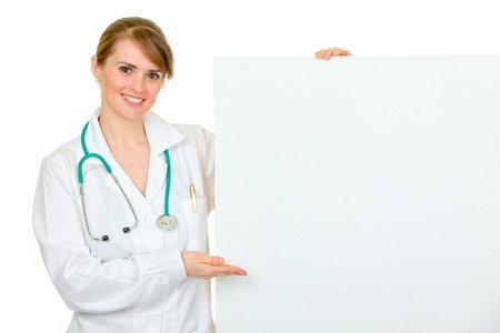 Smiling  medical doctor woman pointing on blank billboard  isolated on white  photo