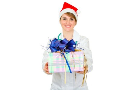 Smiling medical doctor woman in Santa hat holding present in hands isolated on white  photo