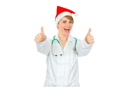heal new year: Happy medical doctor woman in Santa hat showing thumbs up gesture isolated on white