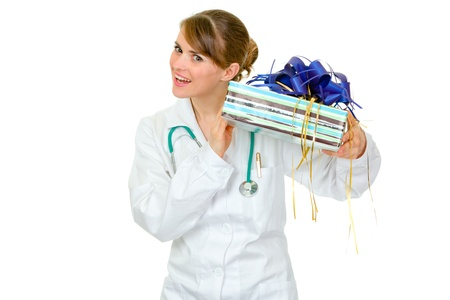 Interested medical doctor woman holding present in hands  isolated on white 