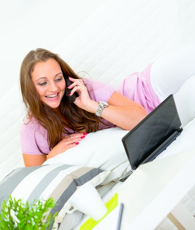 Smiling attractive woman using  laptop on  couch at home and talking on phone   photo