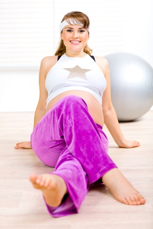 Smiling attractive pregnant woman doing exercise at living room Stock Photo - 9303050