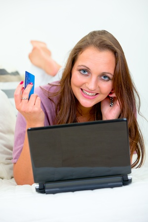 Smiling pretty woman lying on sofa at home and using credit card to shop from net  photo