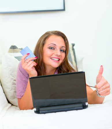 Smiling pretty woman lying on sofa at home with laptop and  credit card and showing  thumbs up gesture  photo