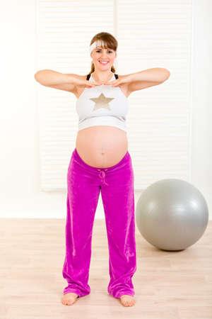 haciendo ejercicio: Sonriendo hermosa mujer embarazada haciendo ejercicio en la sala de estar