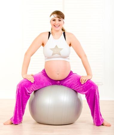 Smiling beautiful pregnant female doing pilates exercises on gray ball  Stock Photo - 9303047
