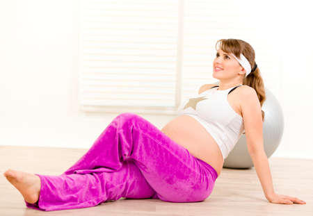 Smiling beautiful pregnant female making gymnastics  at home  photo