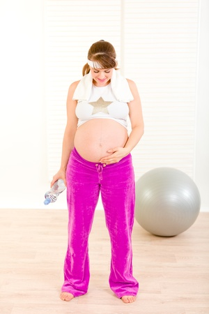 Pregnant woman in sportswear holding bottle of water and looking on her belly