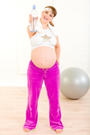 Happy beautiful pregnant female in sportswear holding bottle of  water