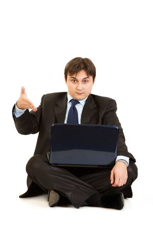 Sitting on  floor with laptop surprised businessman pointing on laptops monitor isolated on white  photo