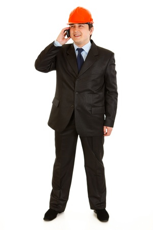 Full length portrait of smiling businessman in helmet on head talking on mobile phone isolated on white  photo