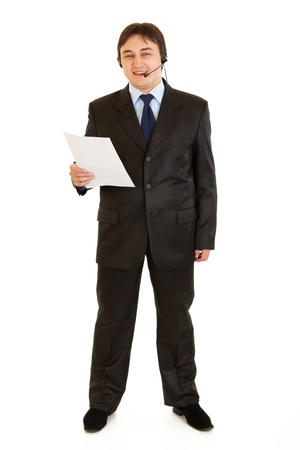 Smiling young businessman with headset holding document in hand isolated on white  photo