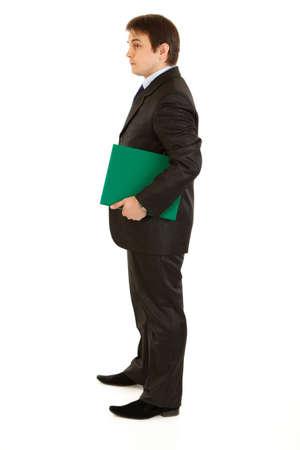 Full length portrait of serious modern businessman holding folder in hand isolated on white  photo