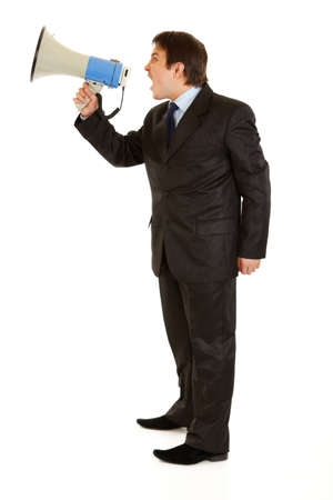 Full length portrait of frustrated young businessman yelling through megaphone isolated on white  photo