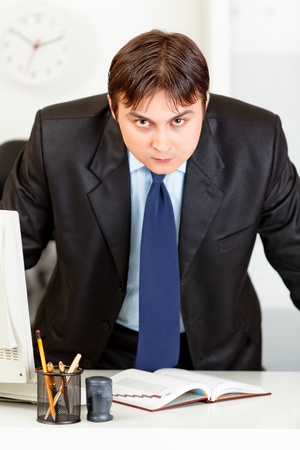 Strict modern business man standing near office desk Stock Photo - 9404007