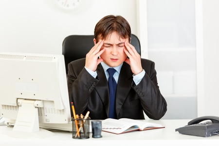 Modern businessman with headache sitting at office desk and holding hands at head  photo