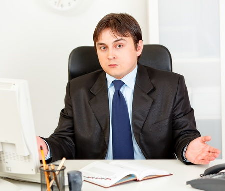 Confused modern business man sitting at office desk Stock Photo - 9403982