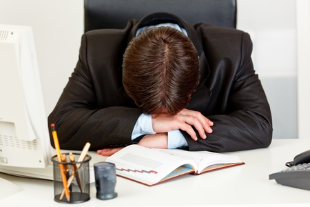 business costume: Tired business man sleeping at  desk in  office   Stock Photo