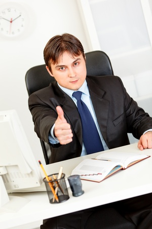certitude: Confident modern business man sitting at office desk and showing thumbs up gesture