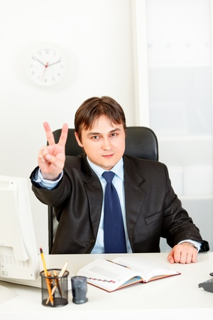 Confident modern business man sitting at office desk and showing victory gesture