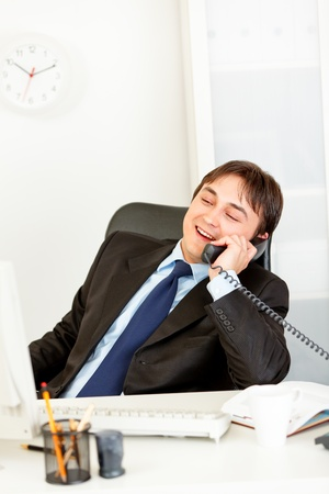 Pleased businessman sitting at office desk and talking on phone Stock Photo - 9403984