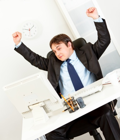 conflicting: Looking at computer monitor business man with conflicting feelings puts hands up   Stock Photo
