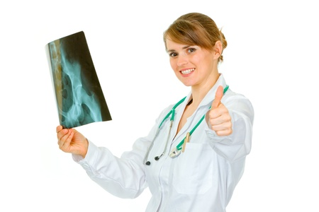 Pleased medical doctor woman holding pelvis roentgen and showing thumbs up gesture  isolated on white