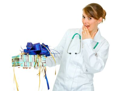 doctor holding gift: Surprised medical doctor woman holding present in hand isolated on white  Stock Photo