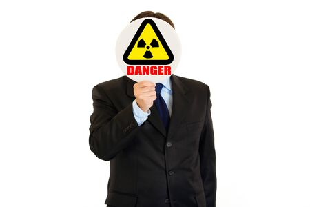 Сoncept- radiation danger! Businessman holding  radiation sign in front of face isolated on white 