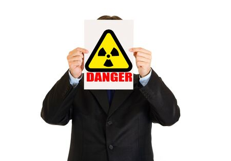 Сoncept-radiation hazard!  Businessman holding radiation sign in front of face Stock Photo - 9465777